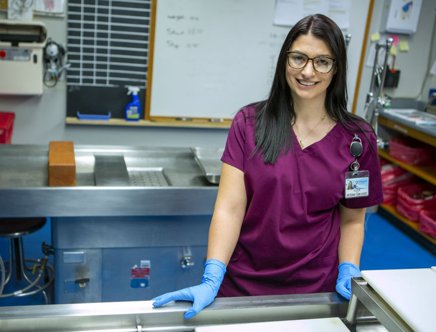 Ally Lewis, supervisor of Decedent Care Services at Hershey Medical Center, smiles as she leans on a metal sink in the autopsy room. Behind her is another medical sink, a bulletin board and equipment on the wall. She has long hair and is wearing scrubs, medical gloves, glasses and an ID badge.