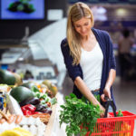 A woman puts vegetables into a shopping basket.