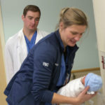 Colin Hayes watches as Jenny Meincke, a registered nurse at Penn State Health St. Joseph Medical Center, leans over while holding a newborn baby. Hayes is wearing a white coat and scrubs. Meincke is wearing a jacket and scrubs. The baby is wrapped in a blanket and has a blue knit cap on his head.