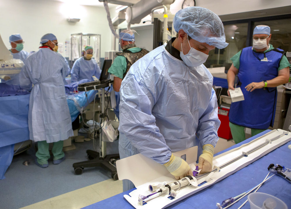 A team of six people from Penn State Heart and Vascular Institute surgeon are in an operating room and preparing for a TAVR procedure. Each are wearing surgical masks, caps and gowns. The man in the foreground is touching a heart catheter device that is lying on a table. Behind him four providers stand around the patient.