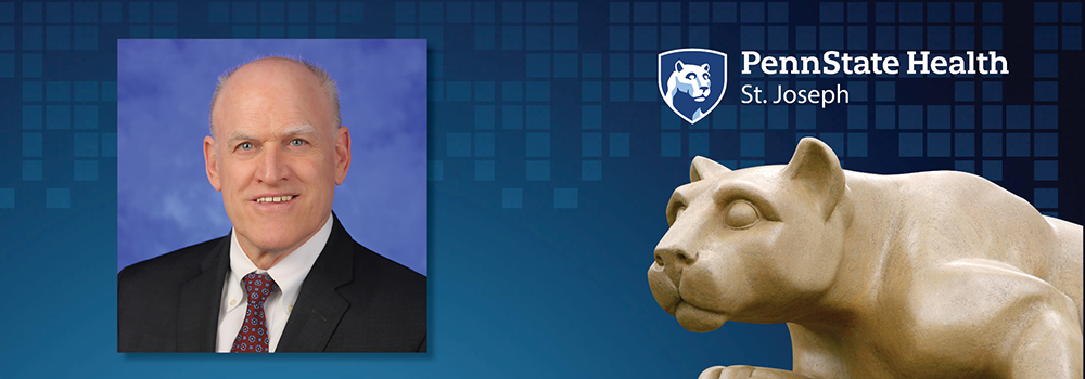 An image of John Morahan is shown next to a statue of the Penn State Nittany Lion.