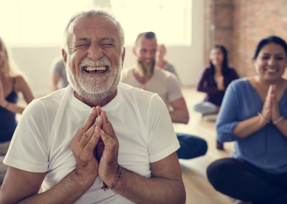 A group of people assume yoga poses and laugh.