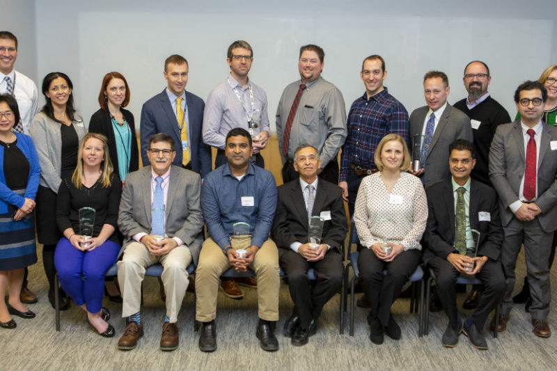 Seventeen people who are the 2019 Teacher of the Year Award recipients at the College of Medicine smile in a group photo. The back row of people are standing, and the front row are seated in chairs. A door is visible on the left.