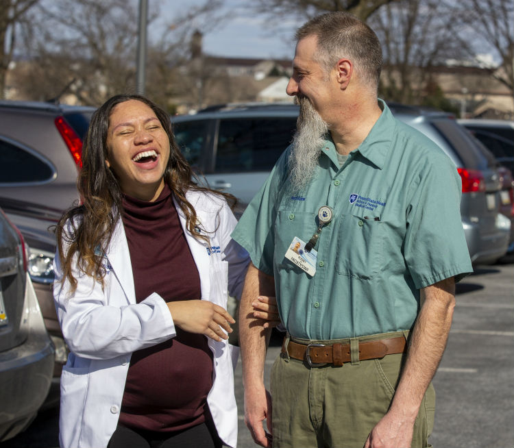 Physician assistant student Tameka Greene, left, and Rod Snell laugh while posing for a photo in the Penn State College of Medicine parking lot. Greene is a young woman with long hair. She is holding Snell's arm and wearing a white lab coat and turtleneck sweater. Snell has a long beard and is wearing a work shirt with the Hershey Medical Center logo on it. Behind them is a row of vehicles.
