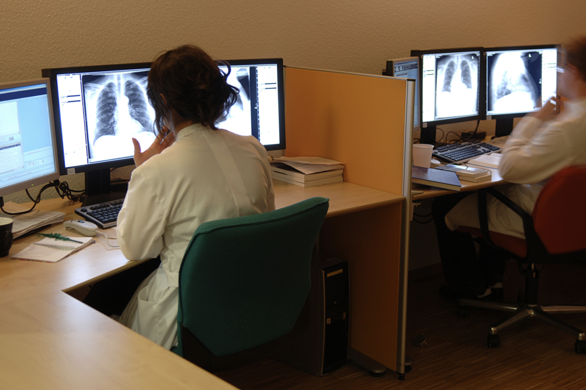 Two people in white coats are seated at computer terminals, looking at x-rays.