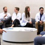 Students in the accelerated (3+) MD pathways at Penn State College of Medicine are pictured in 2019 seated in the lobby of the college on modern-looking chairs. An oblong coffee table is in front of the students. Pictured are, from left, Seth Martin, FM-APPS; Frank Striale, FM-APPS; Dennis Madden, NS-APPS; Elizabeth Zimmerman, IM-APPS; Shannon Brumbaugh, FM-APPS; Alexander Lee, EM-APPS; and Abdel Mohamed, FM-APPS.
