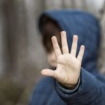 A child wearing a sweatshirt with a hood is seen out of focus and puts his hand up toward the camera.