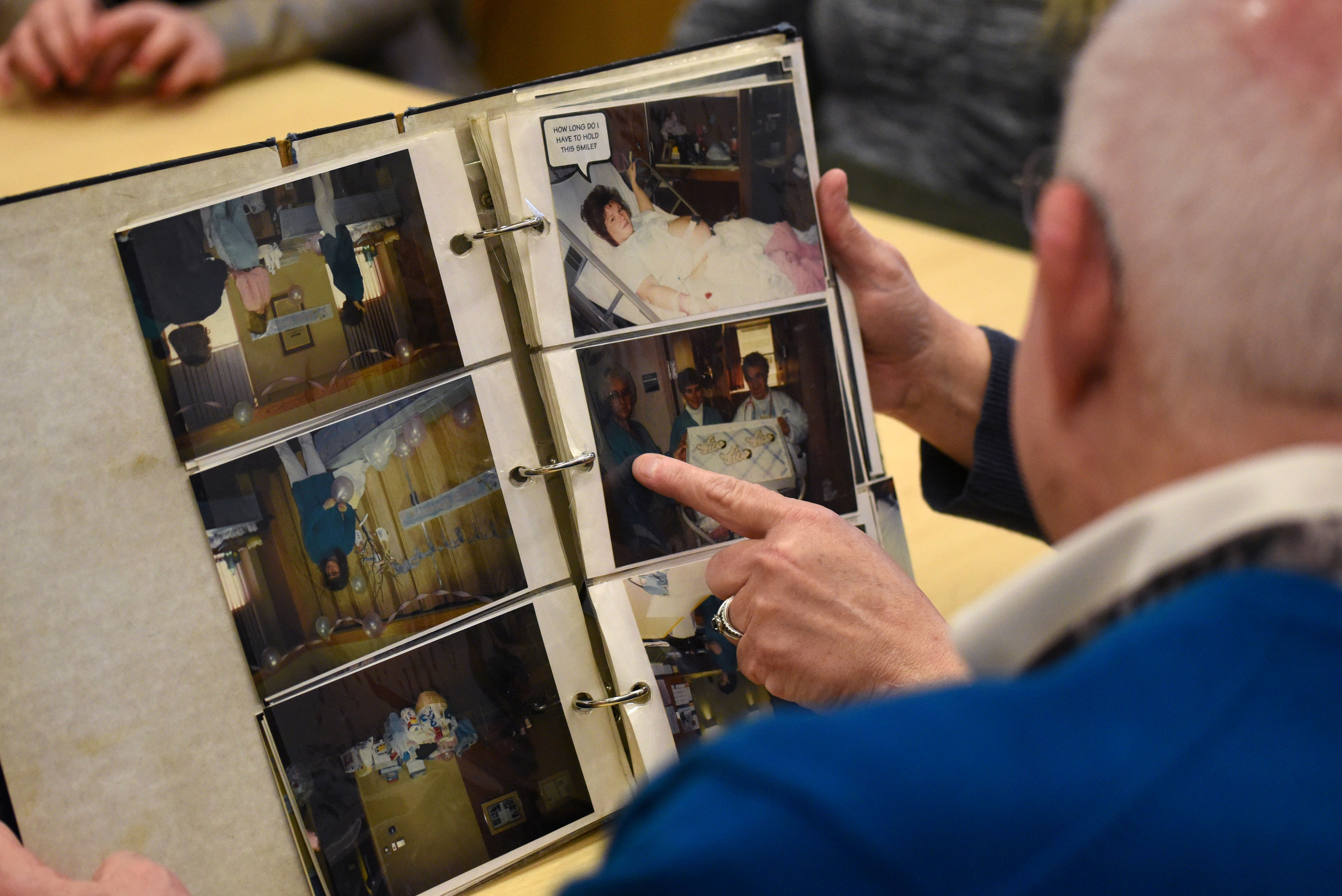 """Janet Boyer looks at photo albums with Dr. Anthony Ambrose, FACOG, at Penn State Health Milton S. Hershey Medical Center on Feb. 29, 2020. Boyer is the mom of Beth Ann, Mackenzie and Emily Schneck, leap year triplets born at the hospital on Feb. 29, 1996. They came back on their """"sixth"""" birthday to tour the new children's hospital expansion."""