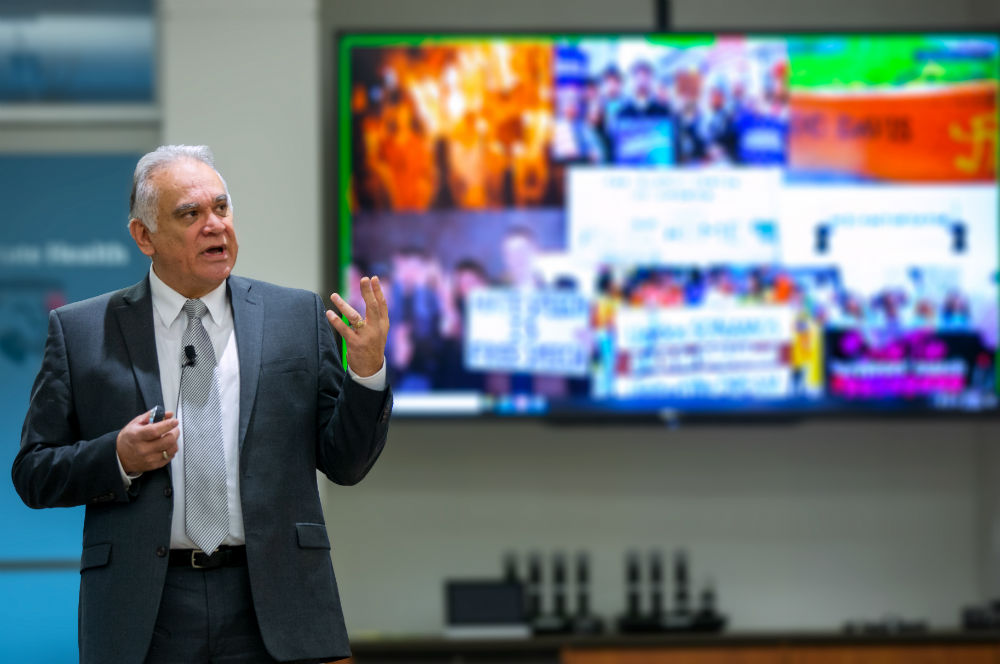 Dr. David Acosta gestures while standing in front of a TV monitor loaded with out-of-focus images. Acosta wears a suit and a microphone is clipped to his tie.