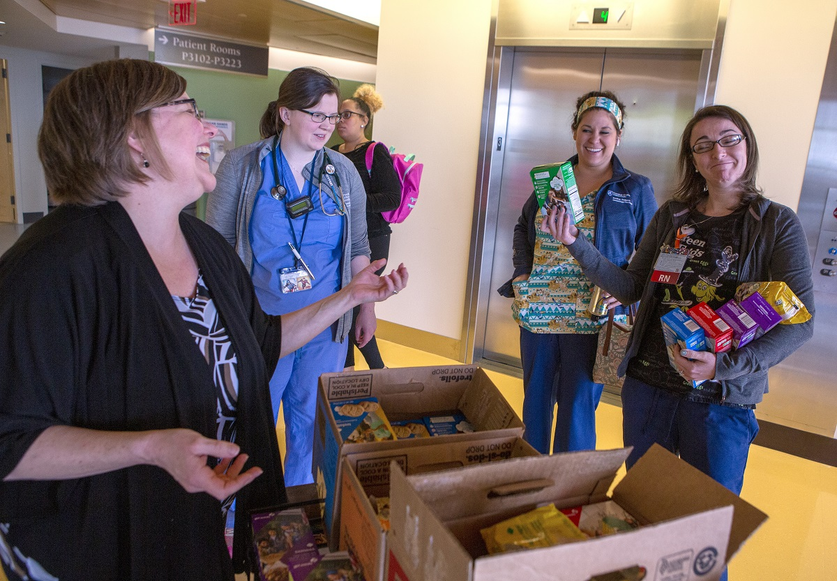 Jill Rebuck laughs at a smiling woman in scrubs holding a stack of Girl Scout cookie boxes. Other women in scrubs look on.