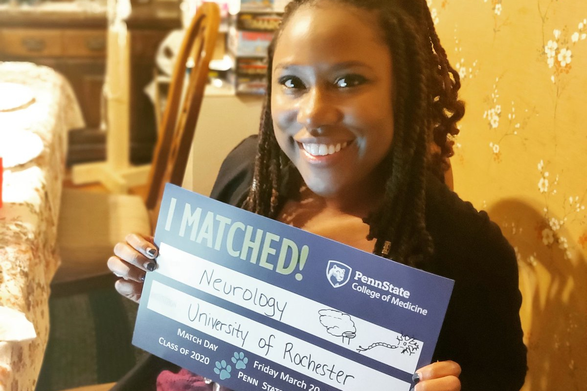 A woman smiles as she holds up a sign that reads: I matched! Neurology; University of Rochester