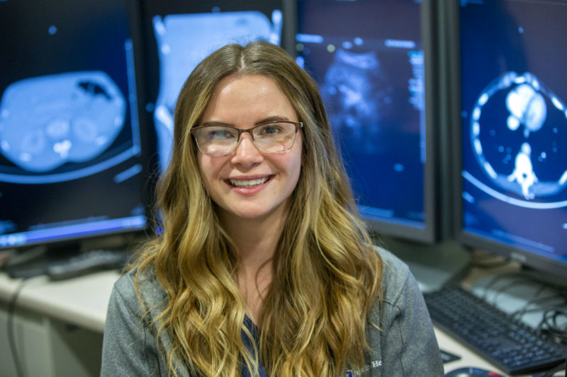 Kassie Heeman, a sonographer at Hershey Medical Center, smiles as she sits in front of desks with four monitors. The monitors have ultrasound images on them. Kassie has long hair and is wearing glasses and a jacket with a Penn State Health logo on it.