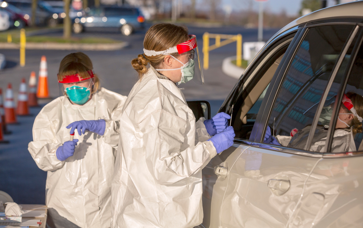 Two nurses wearing personal protective gear administer a car side test for COVID-19