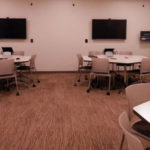 Harrell Health Sciences Library's Experimental Classroom includes round tables with chairs, computers, wall-mounted screens and VR headsets.