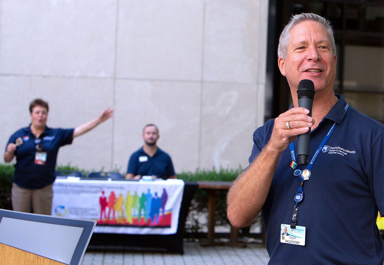 A man speaks into a microphone at an outdoor event. Two people are seen in the background at a table of LGBTQ+ information.