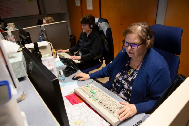 Elaine Allen, foreground, a telephone operator at Hershey Medical Center, sits at a computer wearing a headset and types on a keyboard. Behind her are two other operators.