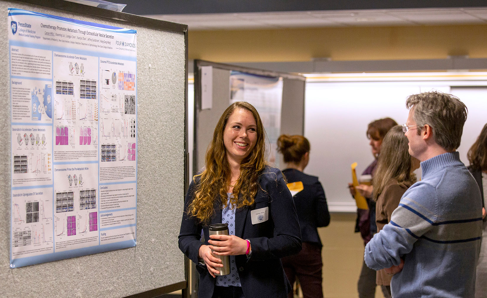 A woman stands near an academic poster, talking and smiling to another person.