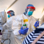 Image shows a healthcare worker in protective gear treating a patient