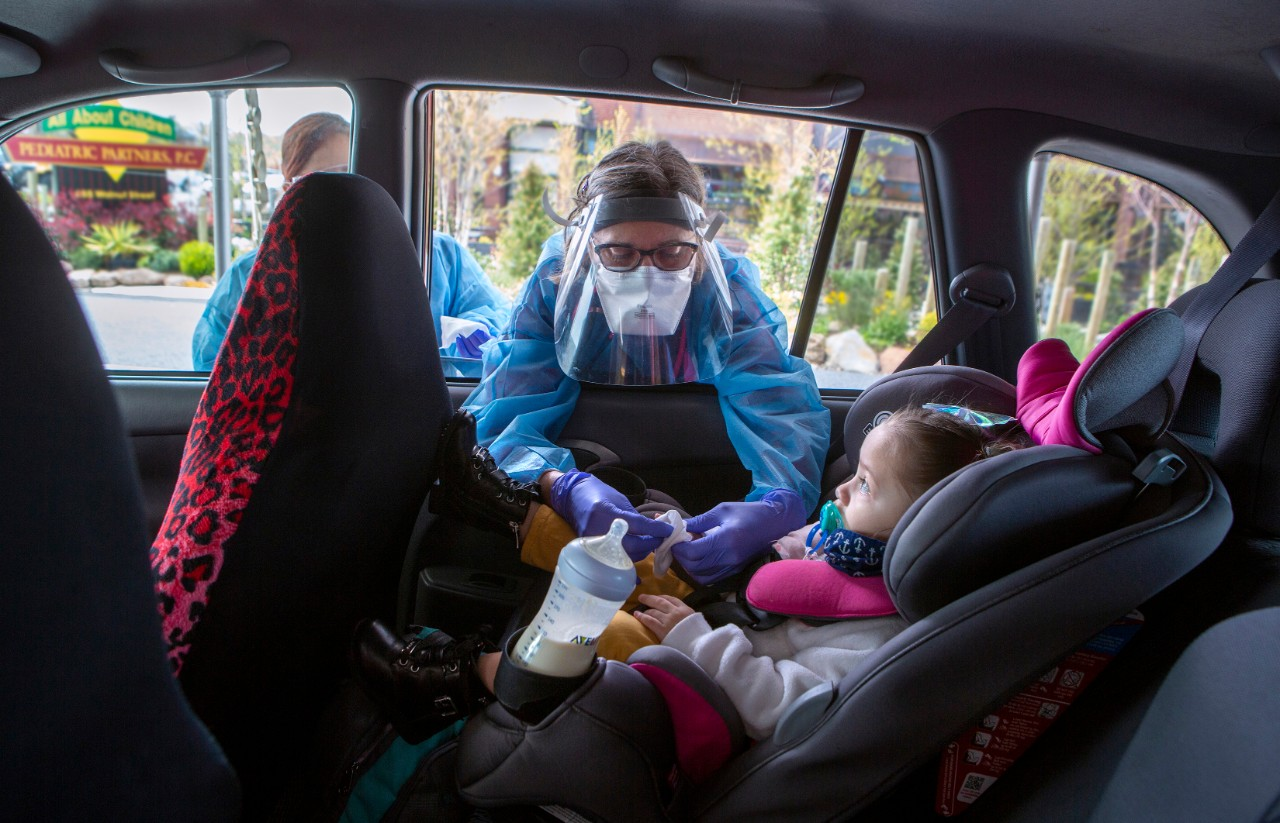 Penny Porter a nurse practitioner with Penn State Health Medical Group ― All About Children, leans into a car and touches the fingers of 2-year-old Zyann Perez-Cruz. Porter is wearing a gown and face shield. The child is in a car seat and has a bottle in the cup holder next to her.