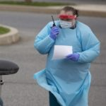 A nurse wearing a gown, gloves and a face shield holds a walkie-talkie as she stands next to a woman in a car. The woman is wearing a face mask.