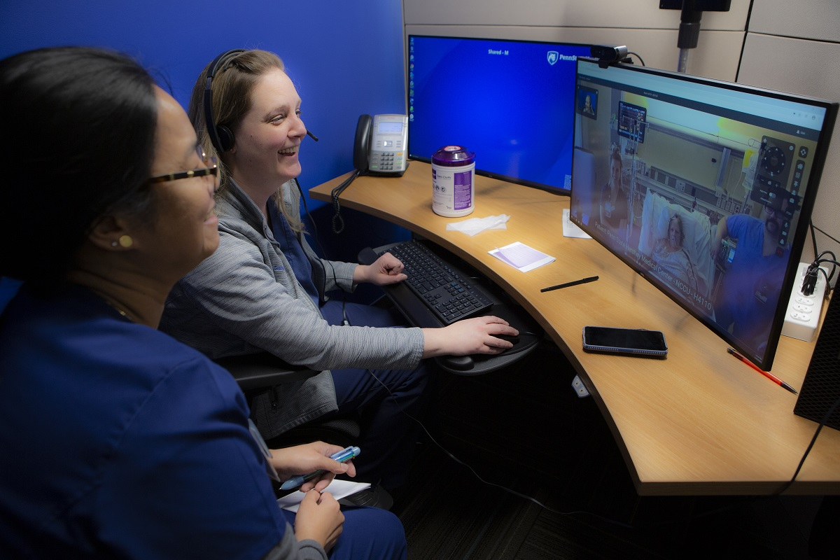 Jennifer Gish, nurse manager, and registered nurse Marilou Magnaye sit at a curved desk and smile at a computer monitor that shows stroke patient Kimberly Laughman in her hospital room in bed, with nurses and equipment around her.