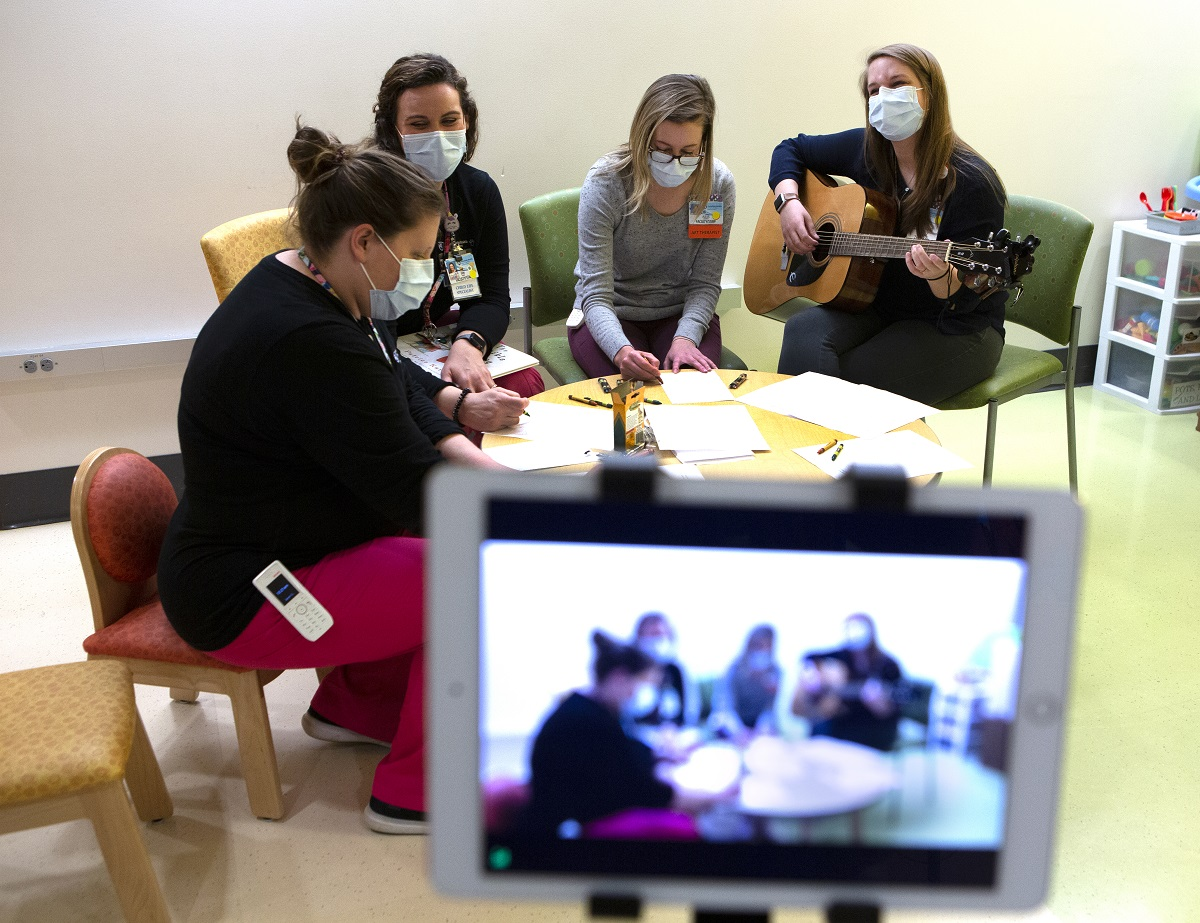 Three Penn State Children's Hospital staff members sit around a child-sized table, coloring with crayons and paper while music therapist Devon Springer strums a guitar. They are all wearing masks. In the foreground is a small screen showing the scene as it is recorded.