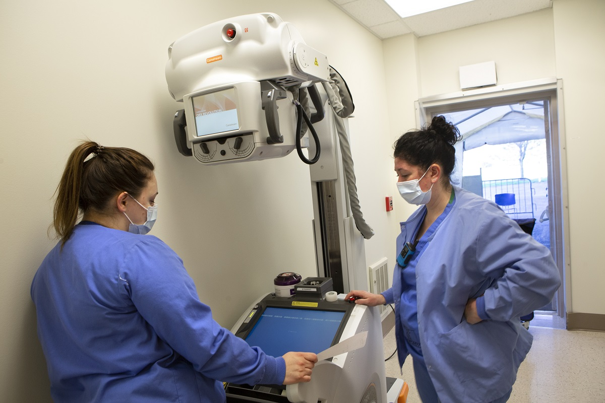 Two radiologic technologists at Hershey Medical Center set up a portable X-ray machine. They are standing by the machine wearing face masks and scrubs. The machine has a large camera on a stand.