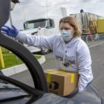 Registered nurse Stephanie McGaw, who is wearing a sweatshirt, gloves and a mask, lifts a cardboard box of food into the trunk of a car. A tractor-trailer truck and traffic cones marking drive-through lanes are in the parking lot behind her.