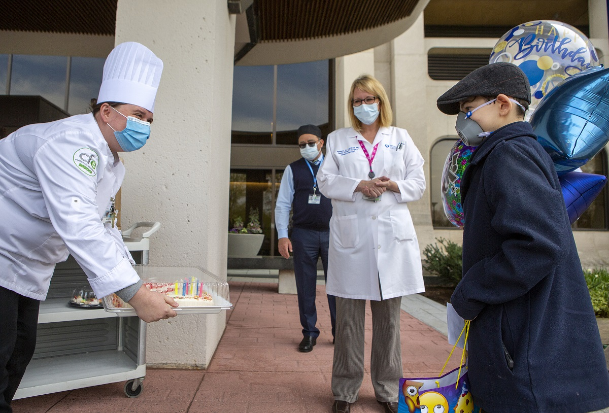 A chef wearing a face mask holds a cake out to a boy who is wearing an N95 mask, a coat and hat. Behind him are balloons, a woman in a white coat and a man.