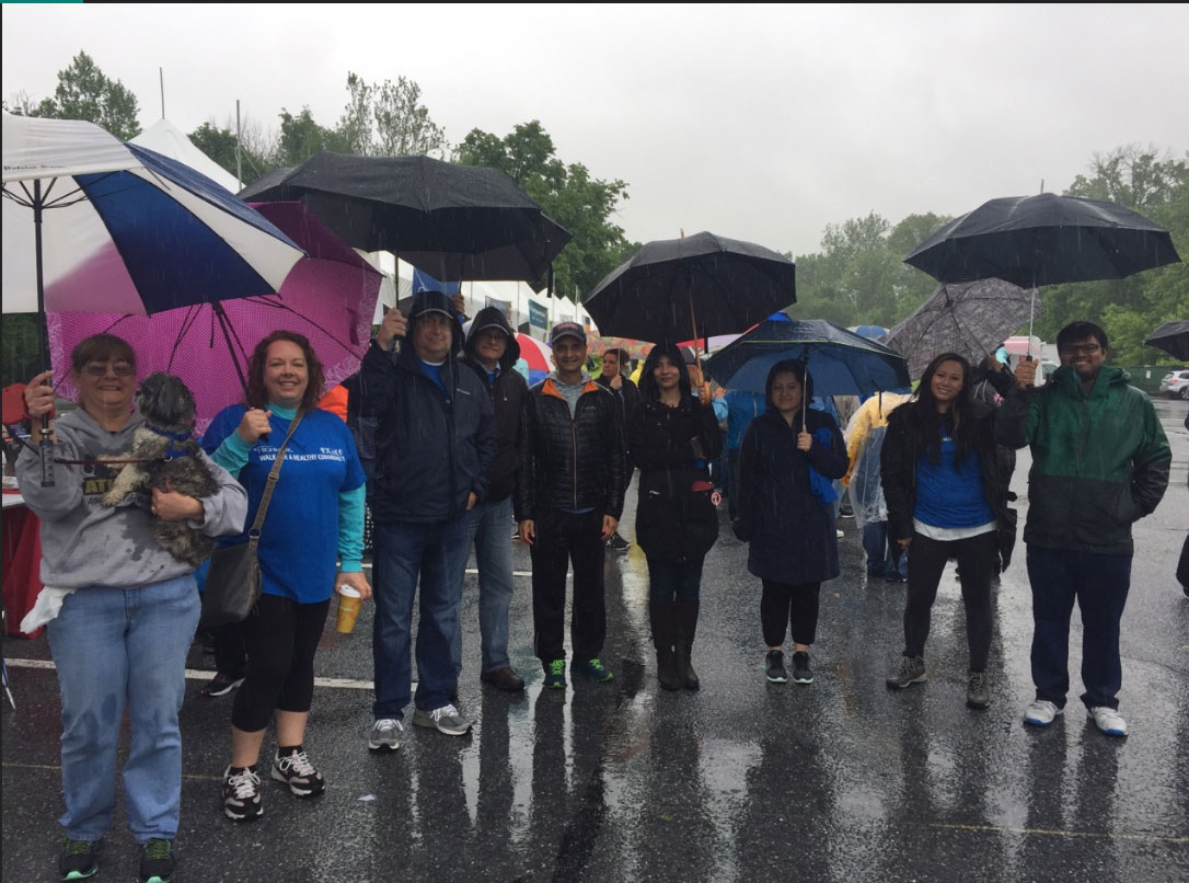 A group of eight people are seen standing outdoors in the rain. They are holding umbrellas.