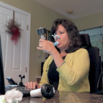 A woman holds a device called a spirometer to her mouth as she looks at a laptop screen. She has medium-length hair and is wearing a sweater. A man is standing to her right.