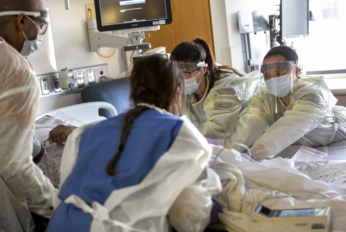 Nancy Rudy and Judylyn Silot, facing camera, from left, registered nurses with the Medical Intermediate Care Unit at Hershey Medical Center, and two other health care workers, whose backs are to the camera, touch a patient who is lying in bed. They are wearing gowns and face shields. Behind them is a monitor.