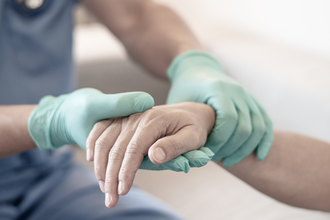 A pair of gloved hands holding another hand without a glove, in a hospital setting.