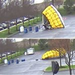 Four different images show a large tent being knocked down by high winds. Barrels and trees are in the foreground.