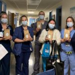 Seven members of the Neonatal Intensive Care Unit are holding bags of coffee. They are all wearing scrubs and masks and standing in the hallway of their unit.