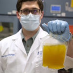 A man wearing a lab coat, gloves and face mask holds up a bag of plasma as he looks at the camera.