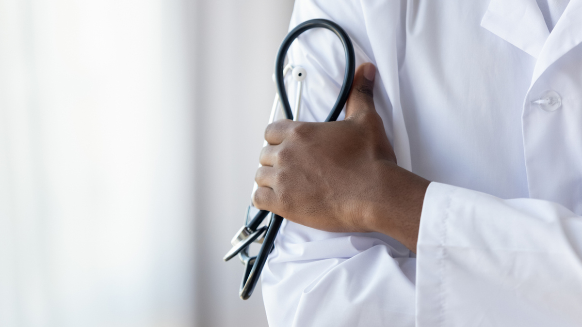 Close-up of doctor's coat with hand holding a stethoscope.