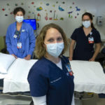 Registered nurses Jamie Boyer, Carol Brown and Kristin Gardyasz, dressed in scrubs and wearing face masks, are standing beside a bed in an exam area. There are stickers and pictures of animals on the walls.
