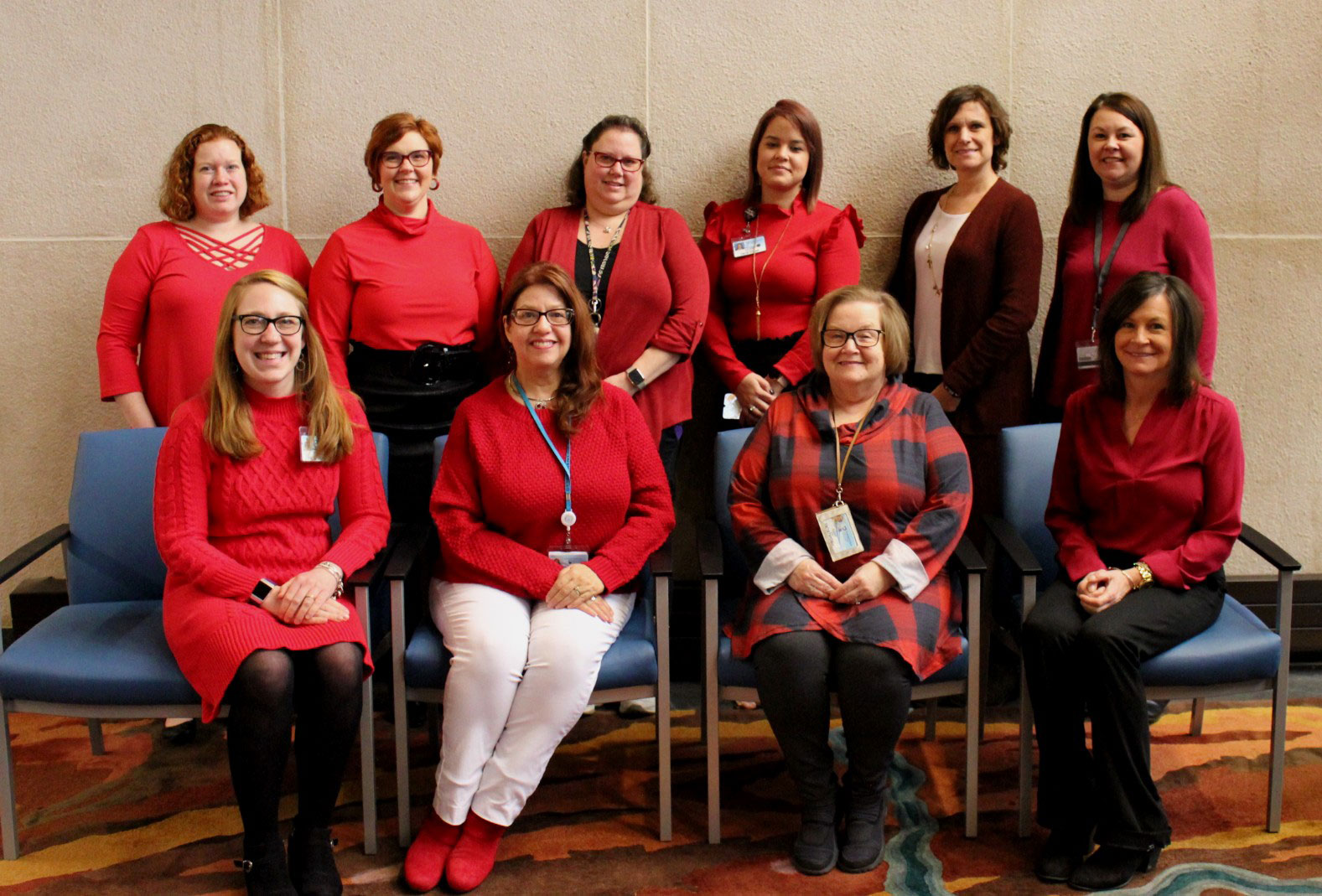 A group of 10 women is seen wearing various shades of red.