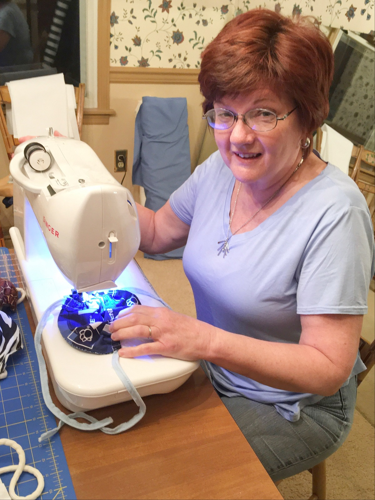 Director of volunteer services Barbara Moyer sits at her sewing machine as she makes a face mask. She is wearing a purple short sleeve shirt, gray pants and glasses.