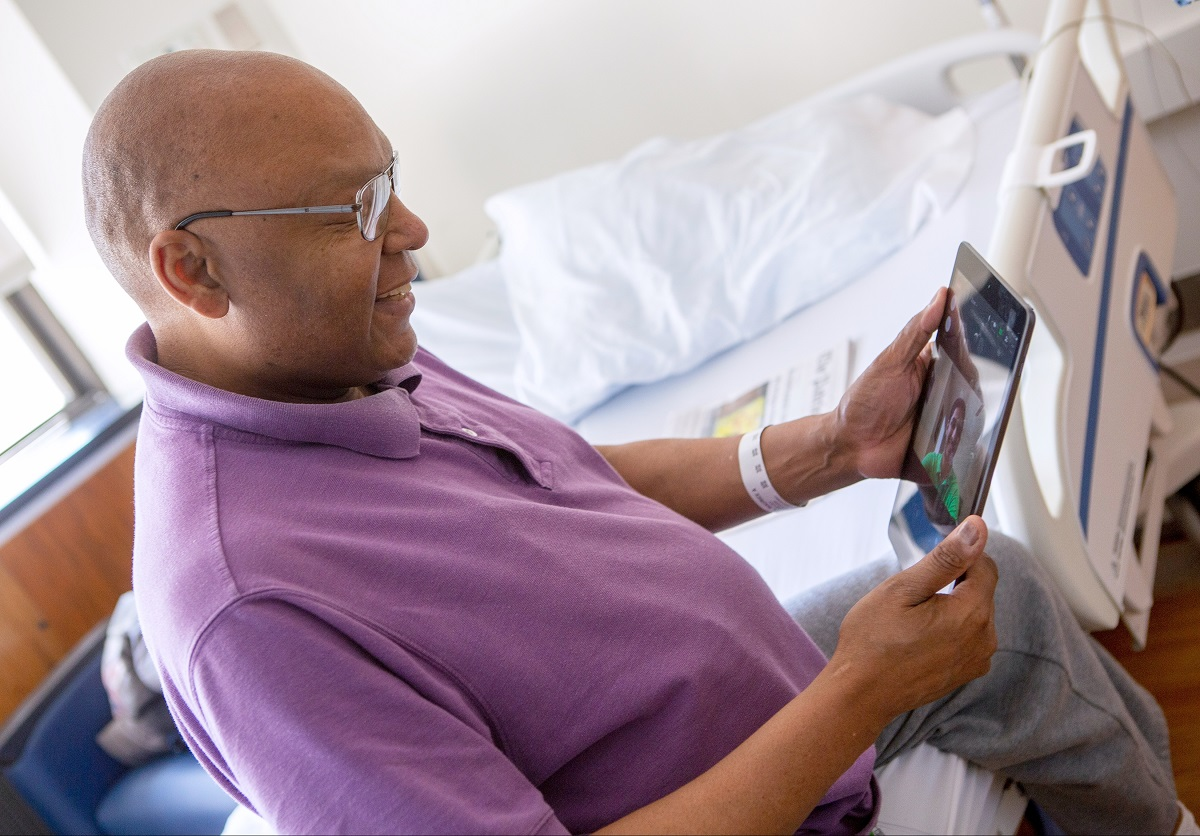 Patient Maurice Brown, who is bald and wears glasses, sits in a chair and smiles down at an iPad in his hands. The screen shows the smiling face of medical student Rahul Gupta. A hospital bed and window are in the background.