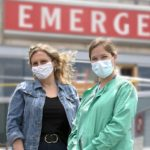"Marie Conley and Kaitlin Snook stand outside the emergency department entrance at Hershey Medical Center. Marie wears a jean jacket and has wavy hair. Kaitlin wears scrubs with her hair in a ponytail. Both wear masks. The word ""emergency"" is on a sign on the building."