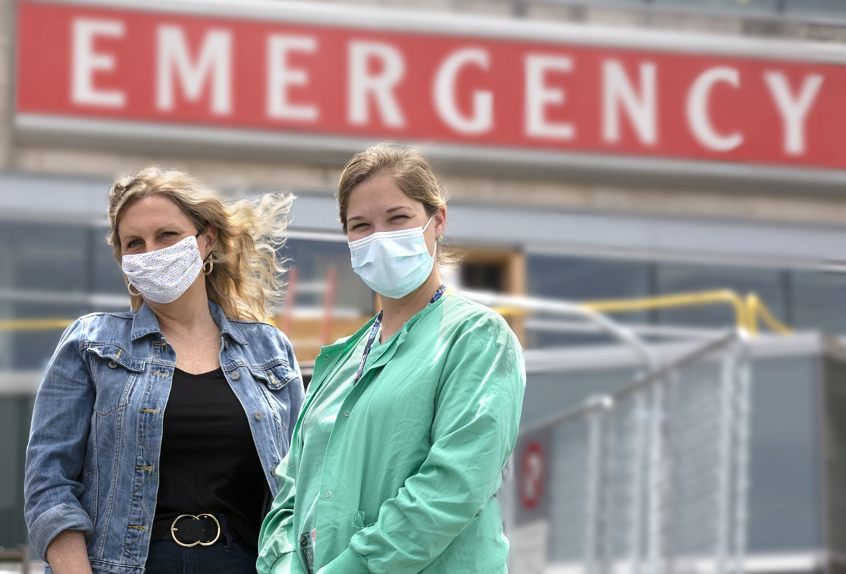 """Marie Conley and Kaitlin Snook stand outside the emergency department entrance at Hershey Medical Center. Marie wears a jean jacket and has wavy hair. Kaitlin wears scrubs with her hair in a ponytail. Both wear masks. The word """"emergency"""" is on a sign on the building."""