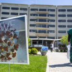 "A health care worker dressed in scrubs and wearing a face mask walks past a curbside sign that shows a graphic of COVID-19 and says ""Brave."" Hershey Medical Center is in the background."