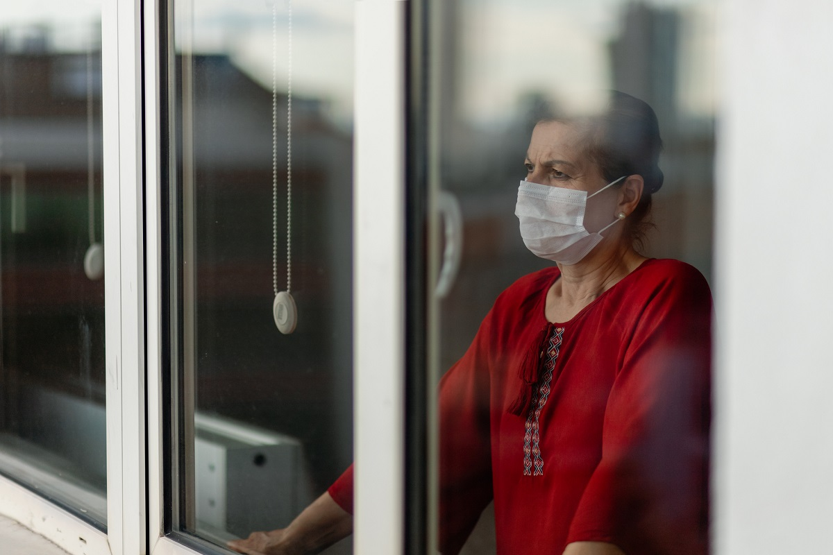 A woman wearing a mask looks out a window. Her brows are furrowed and she looks worried.]