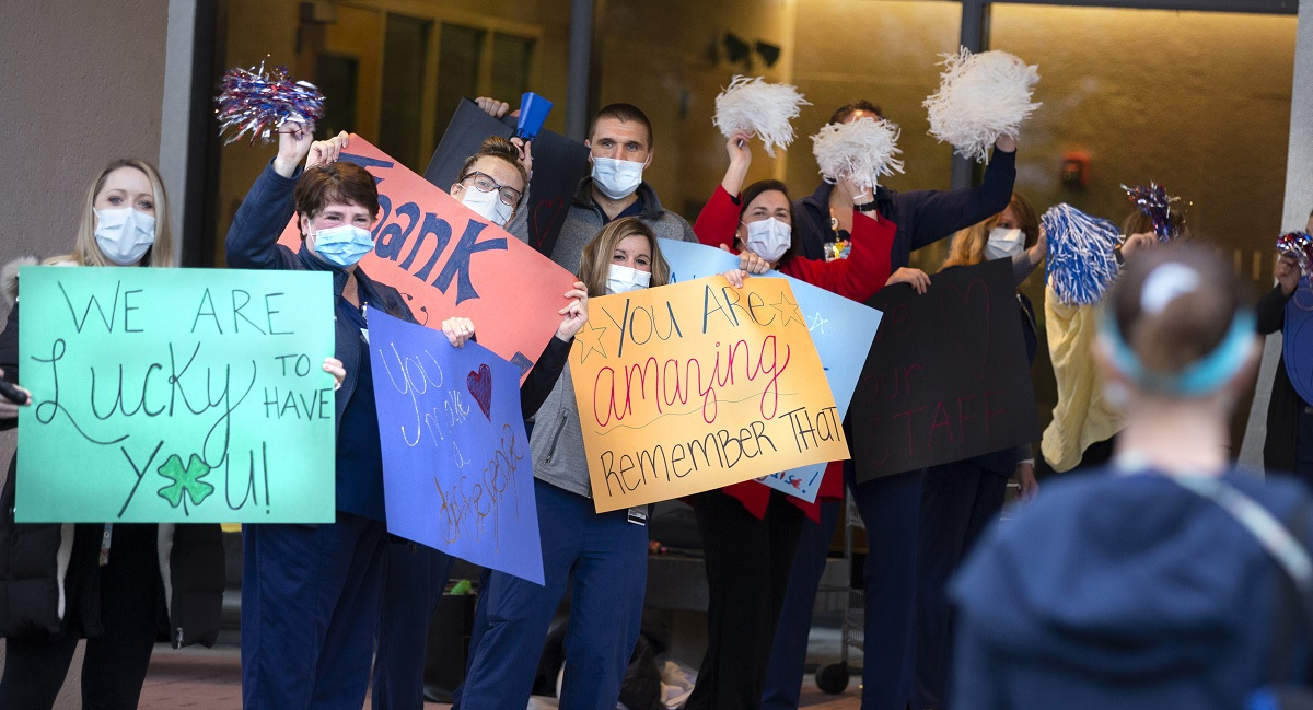 """Hershey Medical Center staff welcome nurses at the entrance holding signs and waving pom poms. The signs read """"We are lucky to have you,"""" and """"You are amazing, remember that"""" and """"thank you."""""""