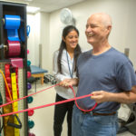 Melanie Potiaumpai, PhD, a postdoctoral scholar with The ONE Group, works with cancer patient Curt Chambers in the exercise room at Penn State Cancer Institute in 2018. Both are smiling and Chambers is pulling on a resistance band.