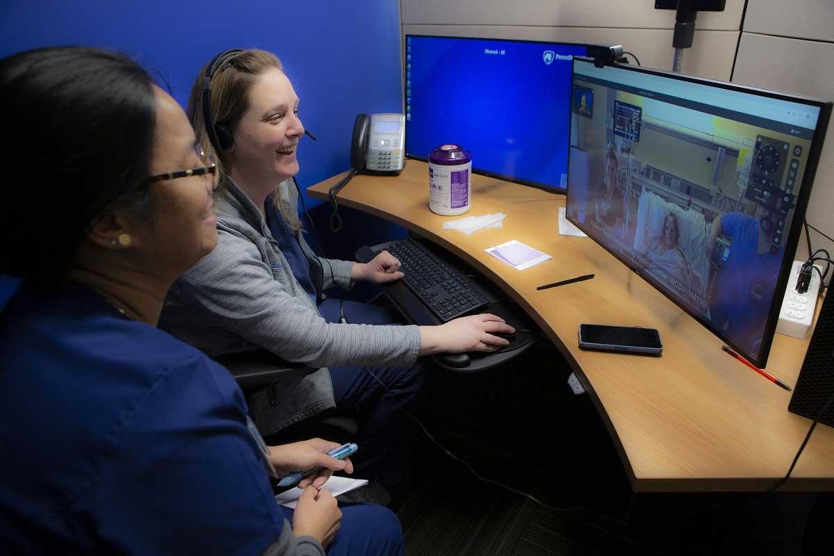 Jennifer Gish, gerente de enfermería y la enfermera registrada Marilou Magnaye se sientan en un escritorio curvo y sonríen al monitor de una computadora que muestra a la paciente con accidente cerebrovascular Kimberly Laughman en su habitación de hospital en la cama, con enfermeras y equipos a su alrededor.