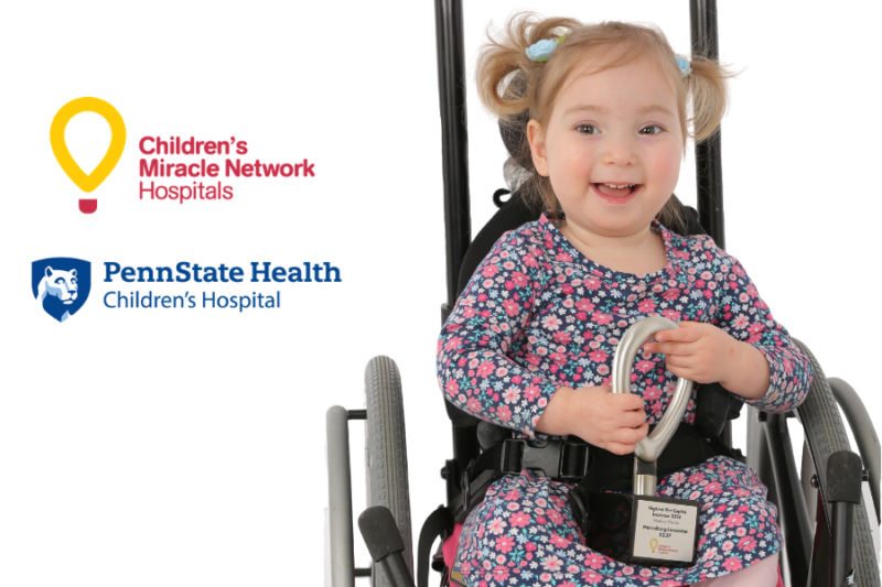 Miracle Child Stella holds a CMN fundraising award in her lap, as she sits in a wheelchair. The CMN Hershey and Penn State Children's Hospital logos appear to her left.