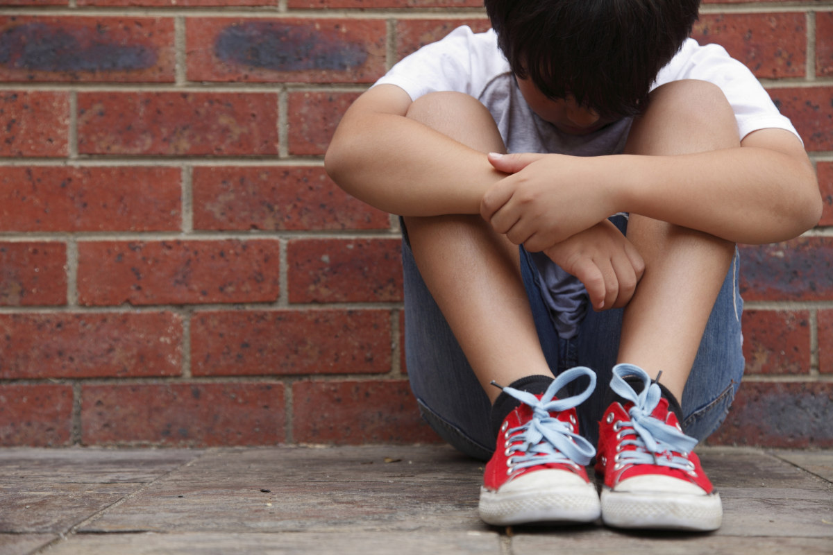 A young boy sits on a sidewalk, leaning against a brick wall, looking down at the ground.